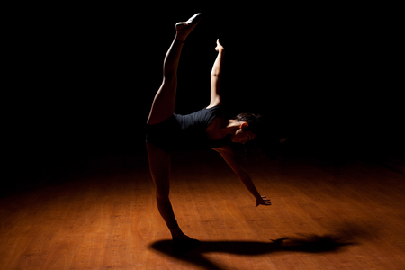 dance pose: Full length view of a good looking young dancer standing in a spotlight in a dark stage and doing a standing leg split