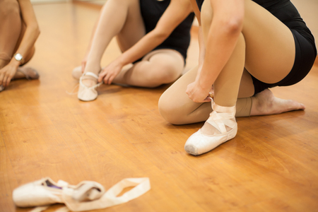 'getting ready': Closeup of a group of young women getting ready for dance practice and putting their shoes on