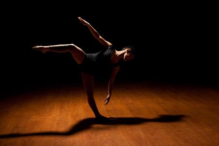 tänzerin: Hübsche junge Tänzerin in einem Scheinwerfer in einer dunklen Bühne zu stehen und über ein Bein Split stehende zu tun Lizenzfreie Bilder