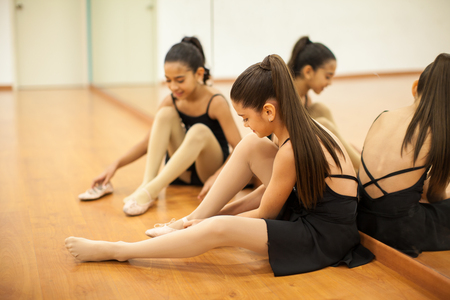 ballerina tights: Two pretty girls putting their shoes on and getting ready for their dance class Stock Photo