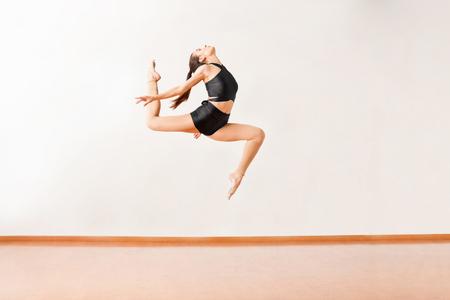 tänzerin: Profil von einer gut aussehenden Tänzerin Springen und eine Pose in der Luft Aufrechterhaltung
