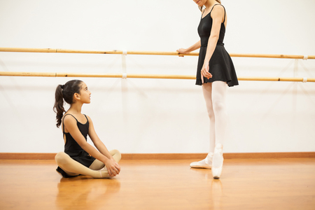 admiration: Dance instructor showing a little girl some ballet moves next to a barre