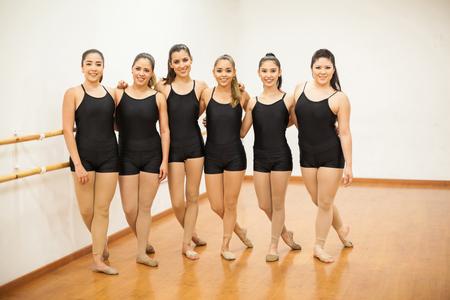 donna che balla: Ritratto integrale di un gruppo di danzatrici in calzamaglia in piedi in uno studio di danza e sorridente