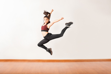 Portrait of a beautiful female jazz dancer jumping in a dance studio and holding a pose
