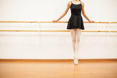 femal: Closeup of a young femal ballet dancer tip toeing next to a barre in a dance studio Stock Photo