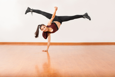 pretty brunette woman: Beautiful female jazz dancer doing a one hand stand and a leg split in the air and smiling in a dance studio