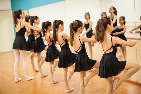 Rij van vele kleine meisjes die deelnemen aan dansles op school en kijken naar kletsen in een spiegel