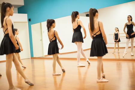 Groep meisjes in maillots en rokken imiteren hun leraar tijdens dansles op school