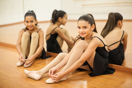 'getting ready': Portrait of a couple of cute girls getting ready for their dance class and smiling Stock Photo