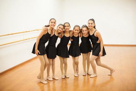 Retrato de cuerpo entero de un grupo de niñas hispanas se unen y que se divierten y sonriente durante la clase de baile Foto de archivo