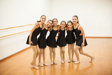 Full length portrait of a group of Hispanic girls standing together and having fun and smiling during dance class