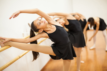 barre: Group of girls stretching with their leg up during a real ballet class at a school
