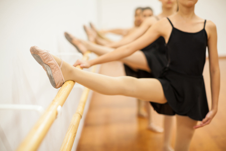 barre: Closeup of a group of girls with their leg up in a barre during a ballet class at school