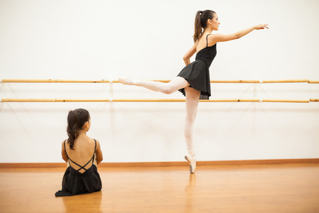 barre: Full length view of a girl sitting and watching her ballet instructor do some barre work as a demonstration for her Stock Photo