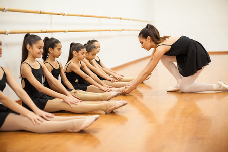 Pretty female dance teacher making sure all her students keep their feet together in a dance class