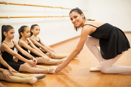 instructor: Portrait of a beautiful young dance teacher helping her students keep their feet together in a dance class