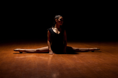 Gorgeous young female dancer doing a leg split on the dance floor in the middle of a performance in a dark stage on a spotlight Banco de Imagens