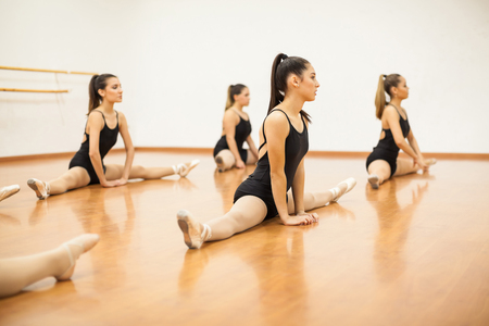 Group of female dancers doing some stretching exercises and warming up for their dance practice Zdjęcie Seryjne - 56599380
