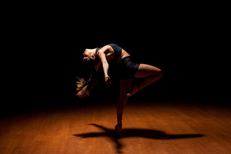 Profile view of a beautiful female jazz dancer showing her dance moves while performing in a dark stage under a spotlight