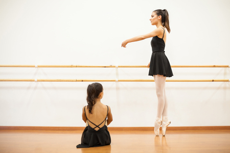 dance studio: Full length view of a little girl sitting and watching a real ballet dancer perform a routine for her