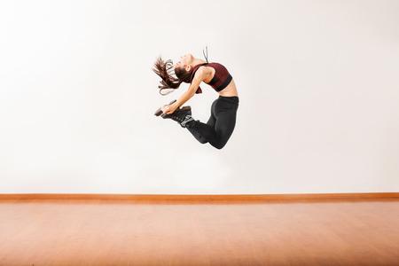 tänzerin: Profilansicht eines athletischen weiblicher Jazz-Tänzer springen und die Durchführung in einem Tanzstudio