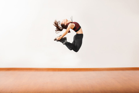 pretty brunette woman: Profile view of an athletic female jazz dancer jumping and performing in a dance studio