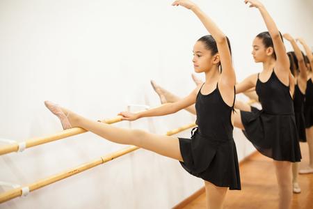 turnanzug: Nettes Mädchen in einem Trikot und Rock ihr Bein und Arm während einer Balletttanz-Klasse heben