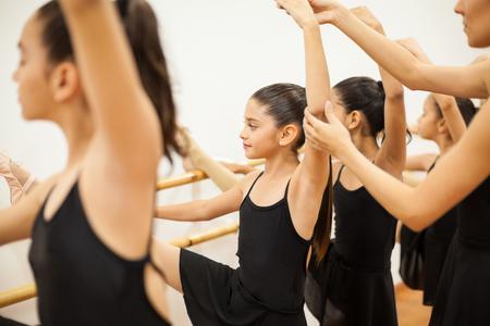 taniec: Portret ładna dziewczyna z jej nogi do góry w Barre i uzyskiwanie pomocy z jej postawy z nauczycielką tańca