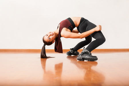 backwards: Beautiful and flexible young jazz dancer bending backwards and smiling in a dance studio Stock Photo