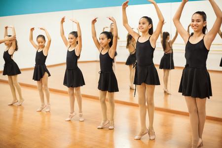 学校でダンスのクラスのいくつかのバレエの練習の女の子のグループ