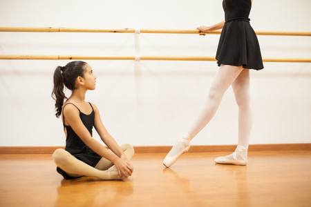 showing: Cute little girl looking up to her dance teacher while she performs a ballet routine next to a barre Stock Photo