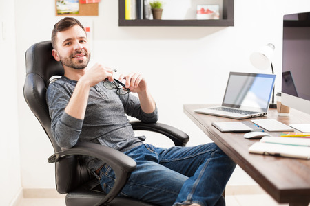 Portrait of a good looking young Hispanic designer leaning back on his chair and taking a break from work