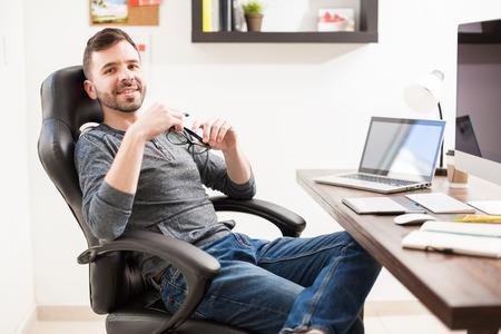 Portret van een goed uitziende jonge Spaanse ontwerper leunend terug op zijn stoel en het nemen van een onderbreking van het werk