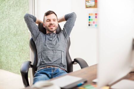 leaning: Portrait of a good looking young man leaning back on his chair and relaxing at his office Stock Photo