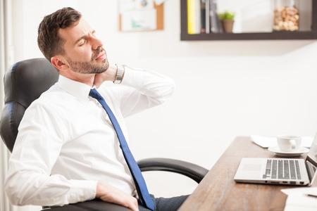 Profil von einer schönen Geschäftsmann mit Nackenschmerzen und Dehnung zu tun, während in einem Büro arbeiten