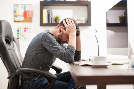 Profile view of a young man with a headache feeling unwell while sitting in front of a computer at the office