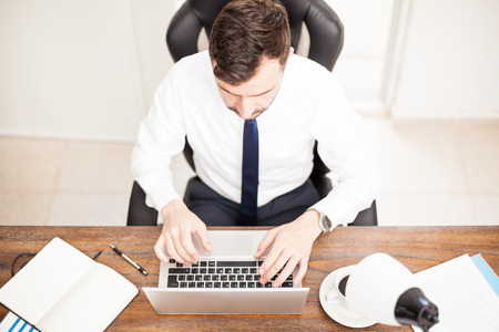 Young businessman working on a laptop in his a trendy office as seen from above Imagens