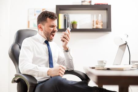 Vista de perfil de un hombre de negocios fuus gritando a un teléfono, mientras que estar en frente de su escritorio en una oficina
