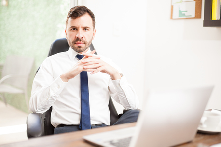 Portrait of a young Hispanic CEO looking powerful and confident while sitting in front of his office desk Stock Photo
