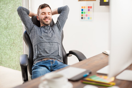 workplace wellness: Handsome young Hispanic man with a beard closing his eyes and relaxing while sitting in front of a computer at a home office