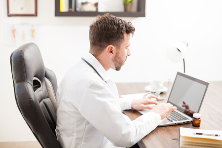 Profile view of a young doctor in a lab coat doing some research on a laptop computer in his office