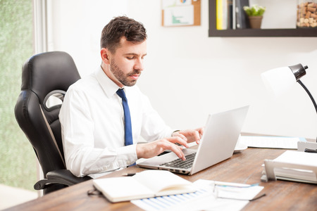 Handsome young attorney typing some legal documents and forms on a laptop computer in his office