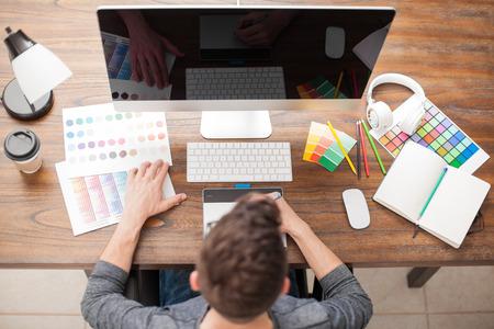 Młody człowiek robi pewne prace projektowe w komputerze stacjonarnym piórem tabletki i próbki kolorów w widoku z góry