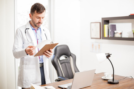 Handsome young doctor with a lab coat and stethoscope reading a patients history while standing in his office Stock Photo