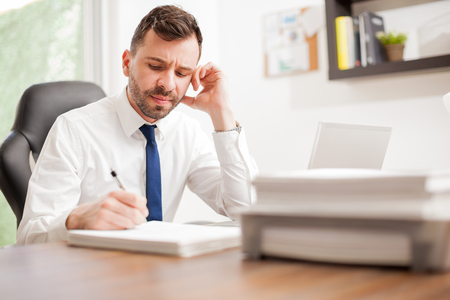 overwhelmed: Good looking attorney overwhelmed at work, signing a pile of documents looking angry and tired