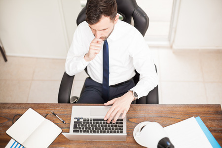 office man: Top view of a good looking young man with a beard working on a laptop computer in his office Stock Photo