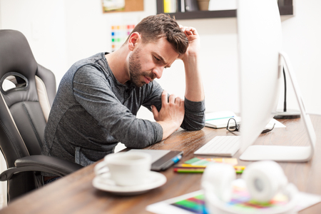 Attractive young man leaning on his desk and trying to clear his head in front of a computer at work