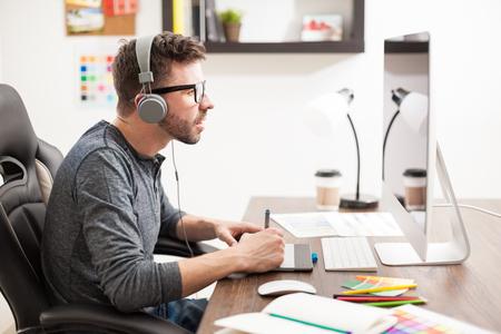 auriculares: Vista de perfil de un joven atractivo haciendo un trabajo de diseño con una tableta de lápiz y una computadora de escritorio mientras se escucha música con auriculares Foto de archivo