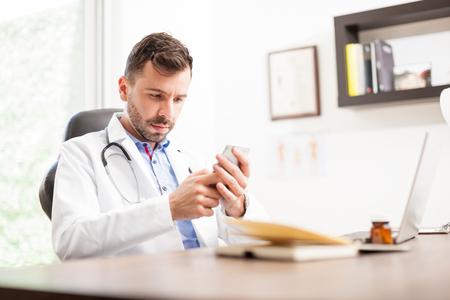 bata blanca: Retrato de un médico guapo con una bata de laboratorio y estetoscopio usando un teléfono inteligente en una oficina