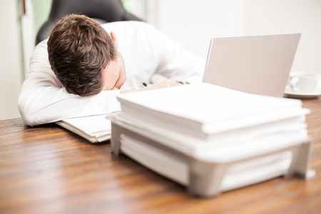 overwhelmed: Portrait of an exhausted young businessman overwhelmed with work and sleeping in the office